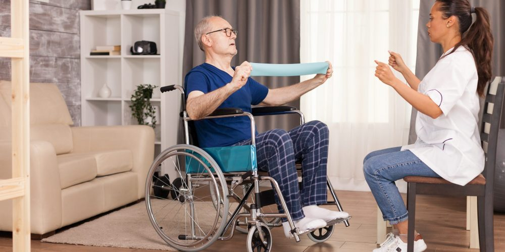 Senior man with disability in wheelchair doing recovery exercise with resistance band. Disabled handicapped old person with social worker in recovery support therapy physiotherapy healthcare system nursing retirement home
